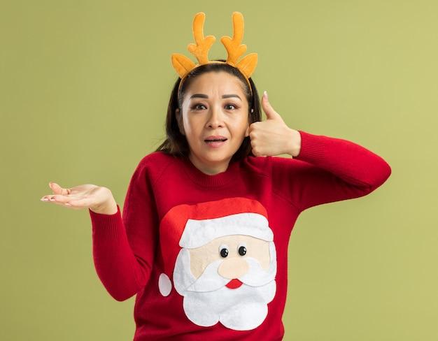 Junge frau im roten weihnachtspullover, der lustigen rand mit hirschhörnern trägt, die überrascht schauen daumen zeigen, die kopienraum mit arm der hand präsentieren