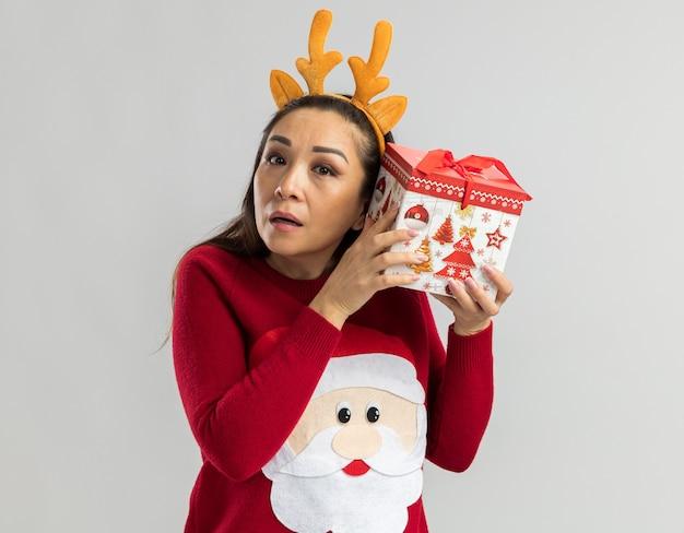 Junge frau im roten weihnachtspullover, der lustigen rand mit hirschhörnern trägt, die weihnachtsgeschenk über ihrem ohr halten, das versucht, etwas zu hören