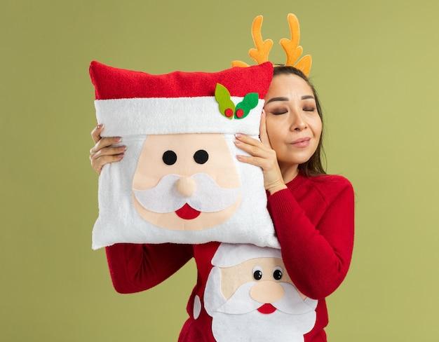 Junge frau im roten weihnachtspullover mit lustigem rand mit hirschhörnern, die weihnachtskissen glücklich und positiv mit geschlossenen augen über grüner wand halten