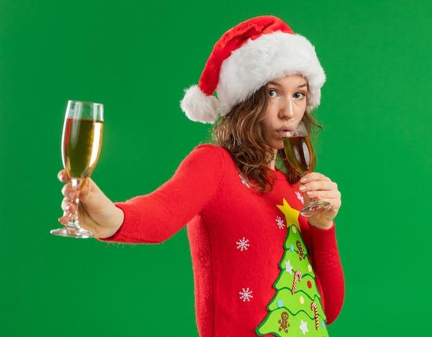 Junge frau im roten weihnachtspullover und in der weihnachtsmannmütze, die zwei gläser des champagnertrinkens hält, der zuversichtlich steht über grünem hintergrund