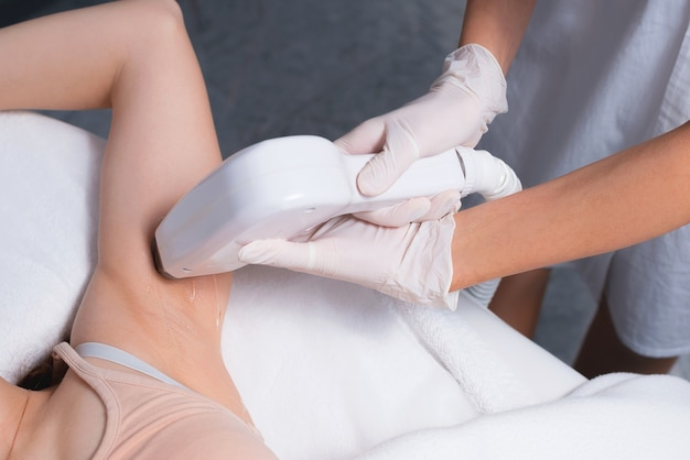 Junge frau im salon mit einem laser-haarentfernungsverfahren auf achselhöhlen