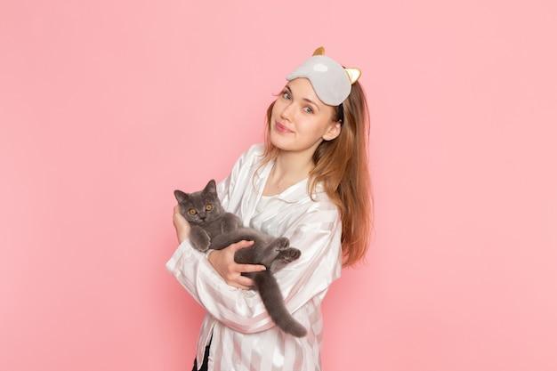 Junge frau im schlafanzug und in der schlafmaske, die mit kätzchen auf rosa aufwirft