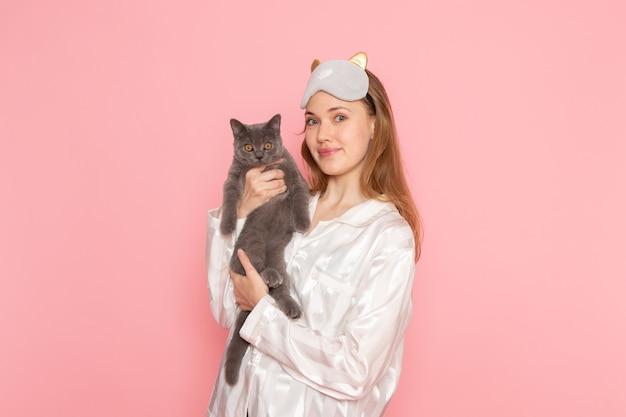 Junge frau im schlafanzug und in der schlafmaske, die niedliche graue katze auf rosa hält