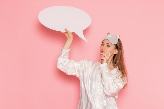 Junge frau im schlafanzug und in der schlafmaske, die weißes zeichen auf rosa hält
