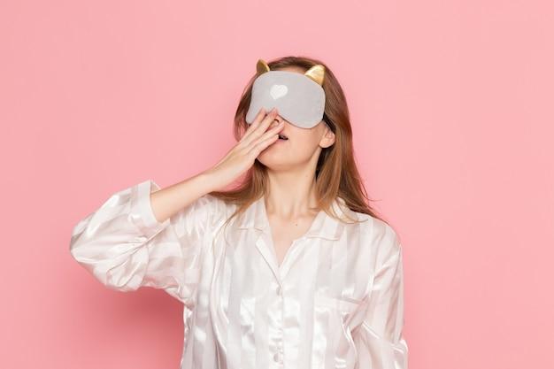 Junge frau im schlafanzug und schlafmaske gähnt damit auf rosa