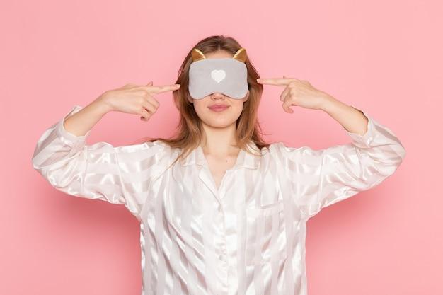 Junge frau im schlafanzug und schlafmaske mit geschlossenen augen auf rosa