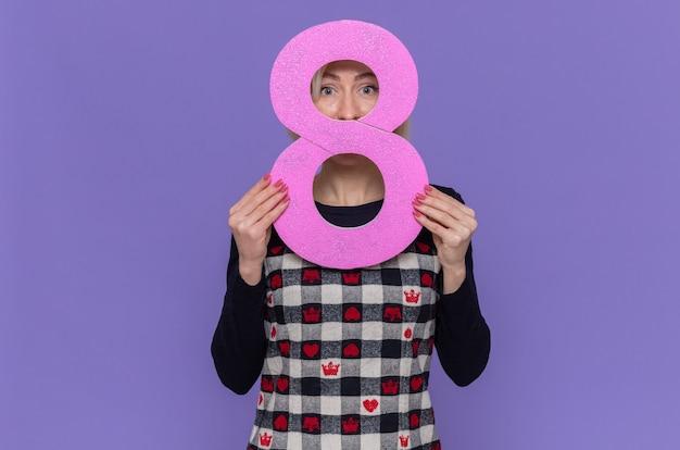 Junge frau im schönen kleid mit der nummer acht aus pappe, die diese nummer mit schüchternem lächeln auf gesicht betrachtet, das internationalen frauentag feiert, der über lila wand steht