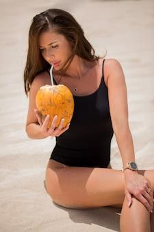 Junge frau im schwarzen badeanzug mit kokosnusscocktail am strand