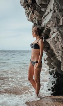 Junge frau im schwarzen bikini, der auf einem sandfelsen nahe dem meer aufwirft. attraktives junges mädchenmodell, das auf vulkanischem strand des schwarzen sandes auf bali aufwirft