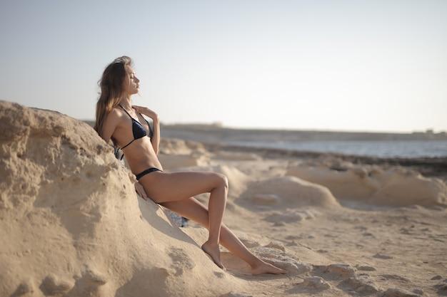 Junge frau im schwarzen bikini, der sich auf den sandigen hügel im strand stützt und die sonne genießt