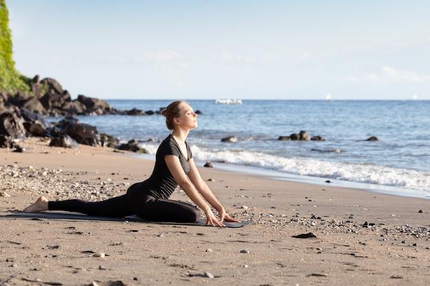 Junge frau im schwarzen, das yoga auf sandstrand tut