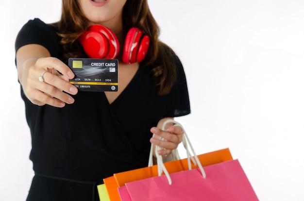Junge frau im schwarzen kleid, das kreditkarte zeigt und einkaufstaschen lokalisiert hält