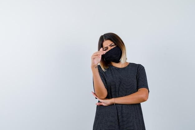 Junge frau im schwarzen kleid, schwarze maske, die auf kamera zeigt. hand unter dem ellbogen halten und ernst aussehen, vorderansicht.
