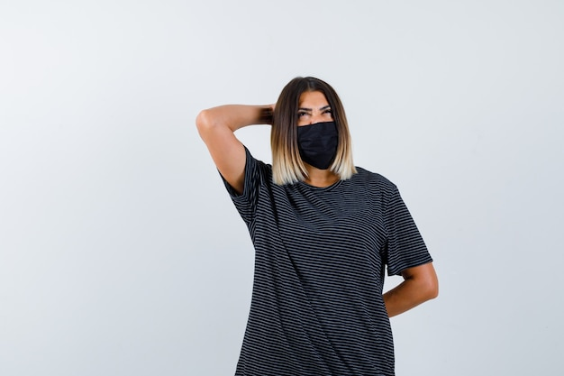 Junge frau im schwarzen kleid, schwarze maske hält eine hand hinter dem kopf, eine andere hand hinter der taille, schaut nach oben und schaut nachdenklich, vorderansicht.
