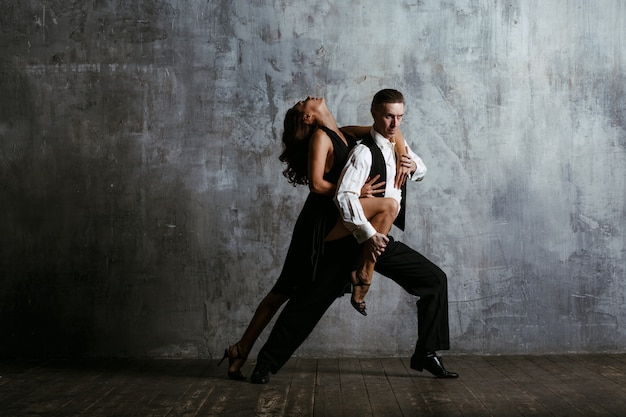Junge frau im schwarzen kleid und im erwachsenen mann, der tango tanzt.