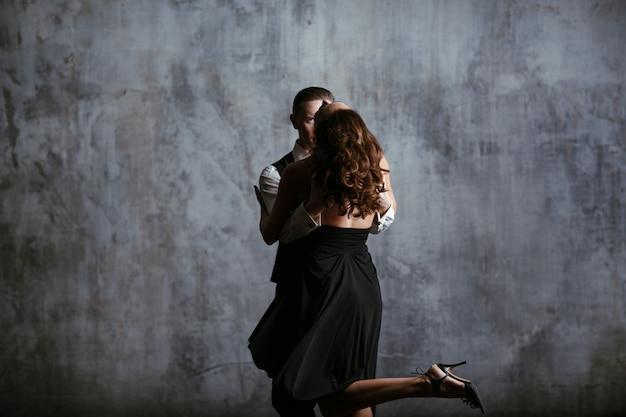 Junge frau im schwarzen kleid und mann tanzen tango