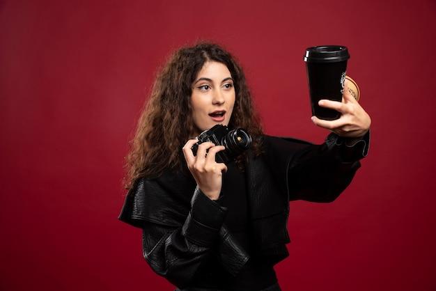 Junge frau im schwarzen outfit, das eine tasse und eine kamera hält.