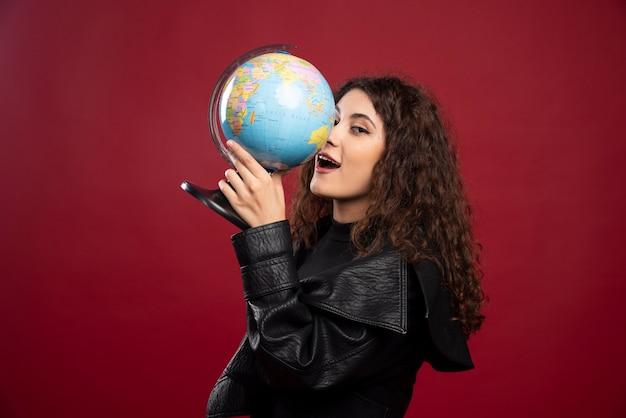 Junge frau im schwarzen outfit, das einen globus hält.