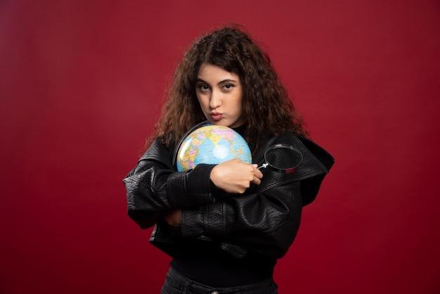 Junge frau im schwarzen outfit, das einen globus mit lupe hält.
