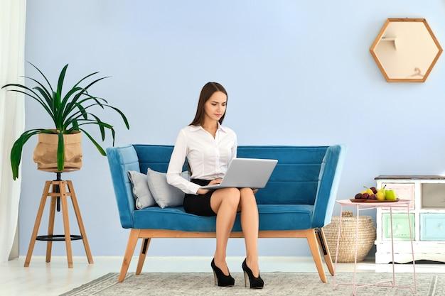 Junge frau im schwarzen rock und in der weißen bluse unter verwendung des laptops beim sitzen auf bequemem sofa