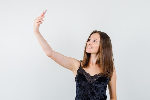 Junge frau im schwarzen unterhemd, das selfie auf handy nimmt und freudig schaut