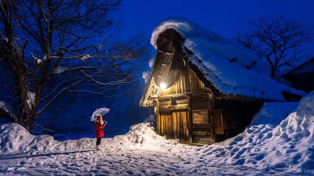Junge frau im shirakawa-go-dorf im winter, japan.