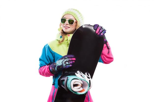 Junge frau im skianzug halten snowboard