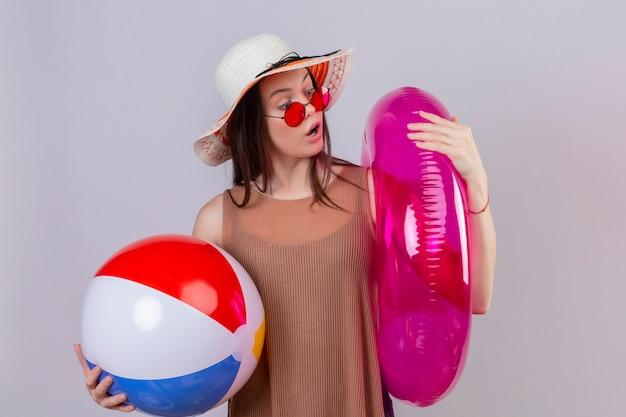 Junge frau im sommerhut, die rote sonnenbrille hält, die aufblasbaren ball und ring hält, die es überrascht betrachten, über weißem hintergrund zu stehen