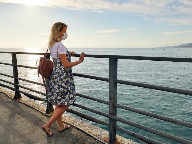 Junge frau im sommerkleid, die auf einem verlassenen pier steht und auf das meer schaut