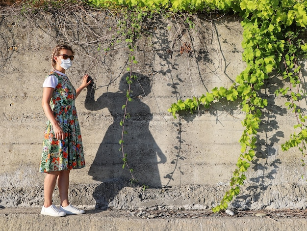 Junge frau im sommerkleid und in der schützenden gesichtsmaske allein steht neben betonwand mit efeu