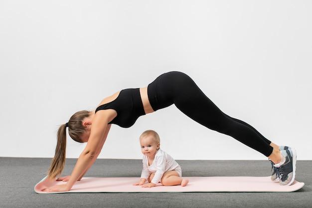 Junge frau im sportbekleidungstraining zusammen mit ihrem baby. glückliche mutter mit sohn, der plank yoga übung macht. konzept des aktiven lebensstils und der mutterschaft