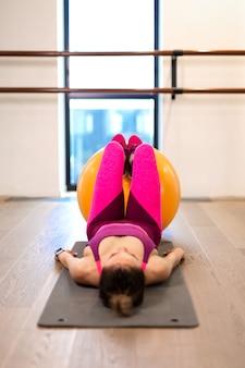 Junge frau im sportwear sportübungsesprit-gelb fitball in der turnhalle. fitness- und wellness-lifestyle-konzept