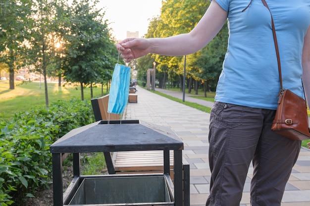 Junge frau im stadtpark nähert sich mülleimer nimmt ihre blaue medizinische schutzmaske ab