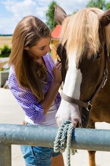 Junge frau im stall mit pferd am sonnenschein