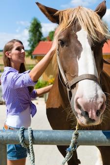 Junge frau im stall oder in der weide mit pferd