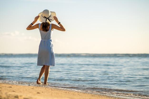 Junge frau im strohhut und in einem kleid, das allein auf leerem sandstrand am seeufer steht