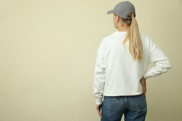Junge frau im sweatshirt und in der mütze gegen beige