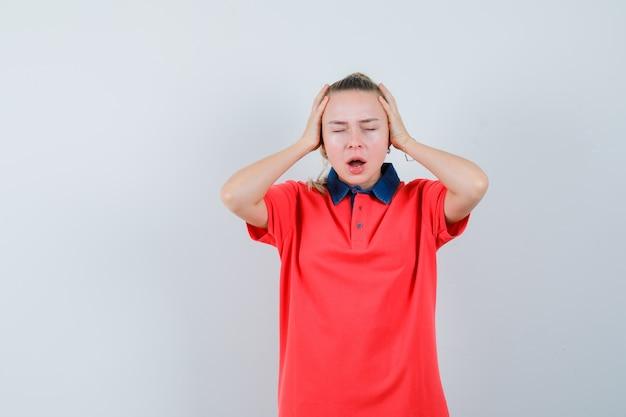 Junge frau im t-shirt, das hände zum kopf hält und deprimiert, vorderansicht schaut.