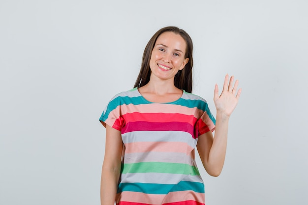 Junge frau im t-shirt, das hand für begrüßung und fröhliche vorderansicht winkt.