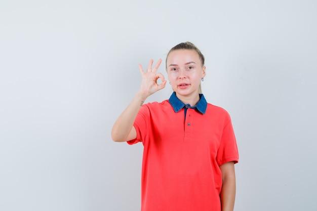 Junge frau im t-shirt, das ok geste zeigt und zufrieden schaut