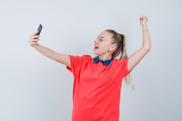 Junge frau im t-shirt, das siegergeste zeigt, während selfie nimmt und munter aussieht