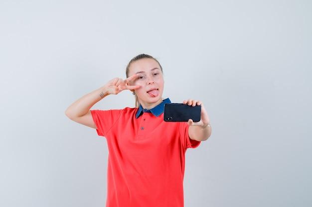 Junge frau im t-shirt, das v-zeichen zeigt, während selfie nimmt und munter aussieht