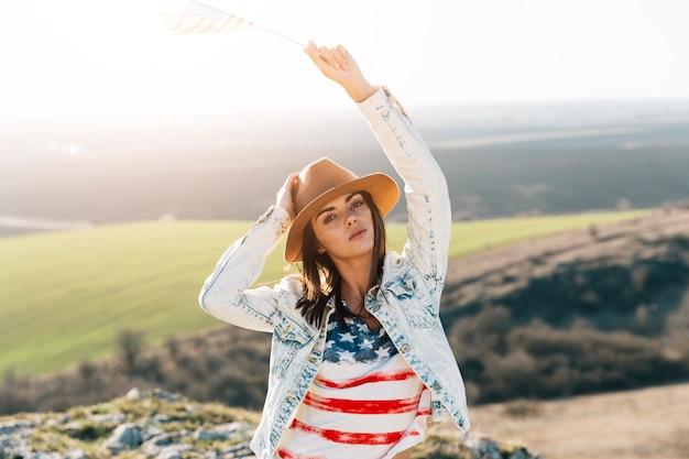 Junge frau im t-shirt der amerikanischen flagge auf berg