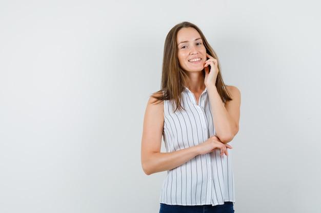 Junge frau im t-shirt, jeans, die auf handy sprechen und glücklich schauen, vorderansicht.