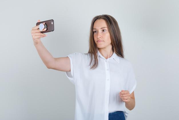 Junge frau im t-shirt, jeans, die selfie am telefon nehmen