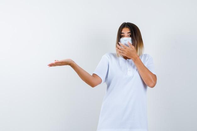 Junge frau im t-shirt, maske, die etwas begrüßt, während hand auf mund hält und selbstbewusst, vorderansicht schaut.