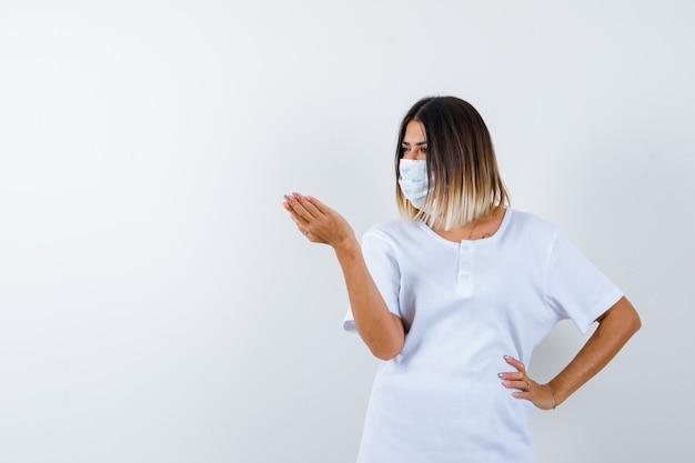 Junge frau im t-shirt, maske, die hand in fragender geste streckt, während hand auf taille hält und ernsthafte vorderansicht schaut.