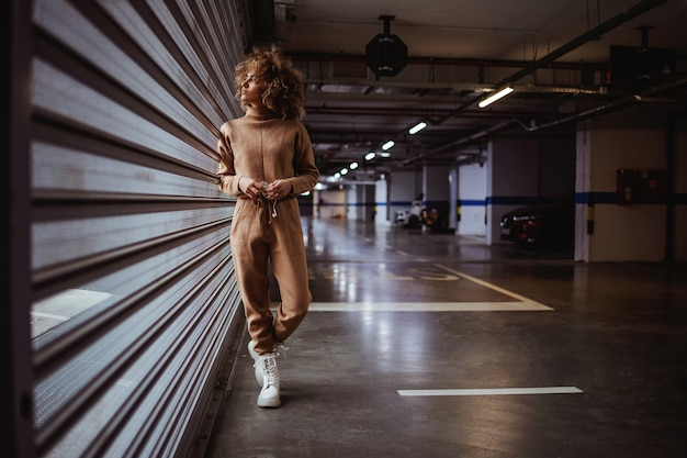 Junge frau im trainingsanzug, der gegen das garagentor steht und durch es schaut