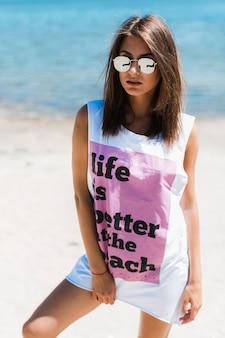 Junge frau im übergroßen trägershirt auf strand