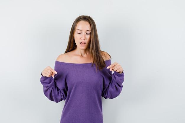 Junge frau im violetten hemd, das nach unten zeigt und fokussierte vorderansicht schaut.